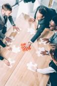 vysoký úhel pohledu mnohonárodnostní podnikatelé sestavování puzzle na konferenční stůl
