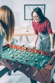 Fotografie young attractive businesswomen playing table football in modern office