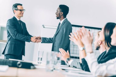 multiethnic businessmen shaking hands in conference hall with partners sitting at table and claping hands