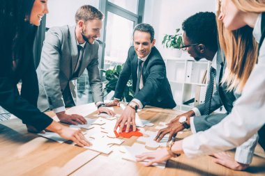 multiethnic businesspeople assembling puzzle together in conference hall