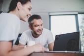 Lächelndes Paar blickt auf Laptop mit leerem Bildschirm in Küche