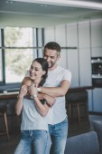 laughing man embracing girlfriend from behind in kitchen at home