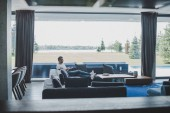 Fotografie Fernsicht auf männlichen Freiberufler arbeiten mit Laptop zu Hause auf sofa