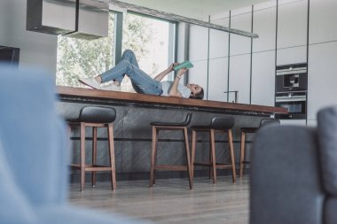 surface level of woman laying on table and reading book in kitchen at home