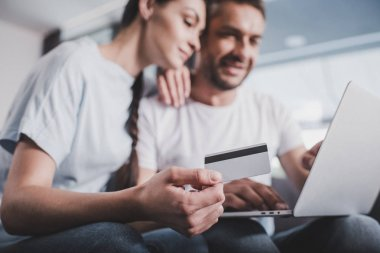 selective focus of smiling couple with laptop doing online shopping by credit card at home