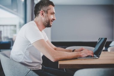 side view of handsome male freelancer using laptop with blank screen at home