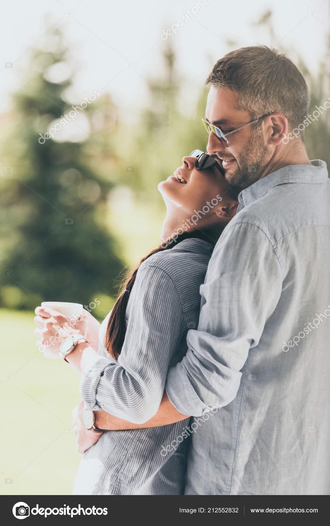d1ffd9079efae1 Vue latérale d un homme heureux en lunettes de soleil embrassant copine  avec une tasse de café en plein air — Image de ArturVerkhovetskiy