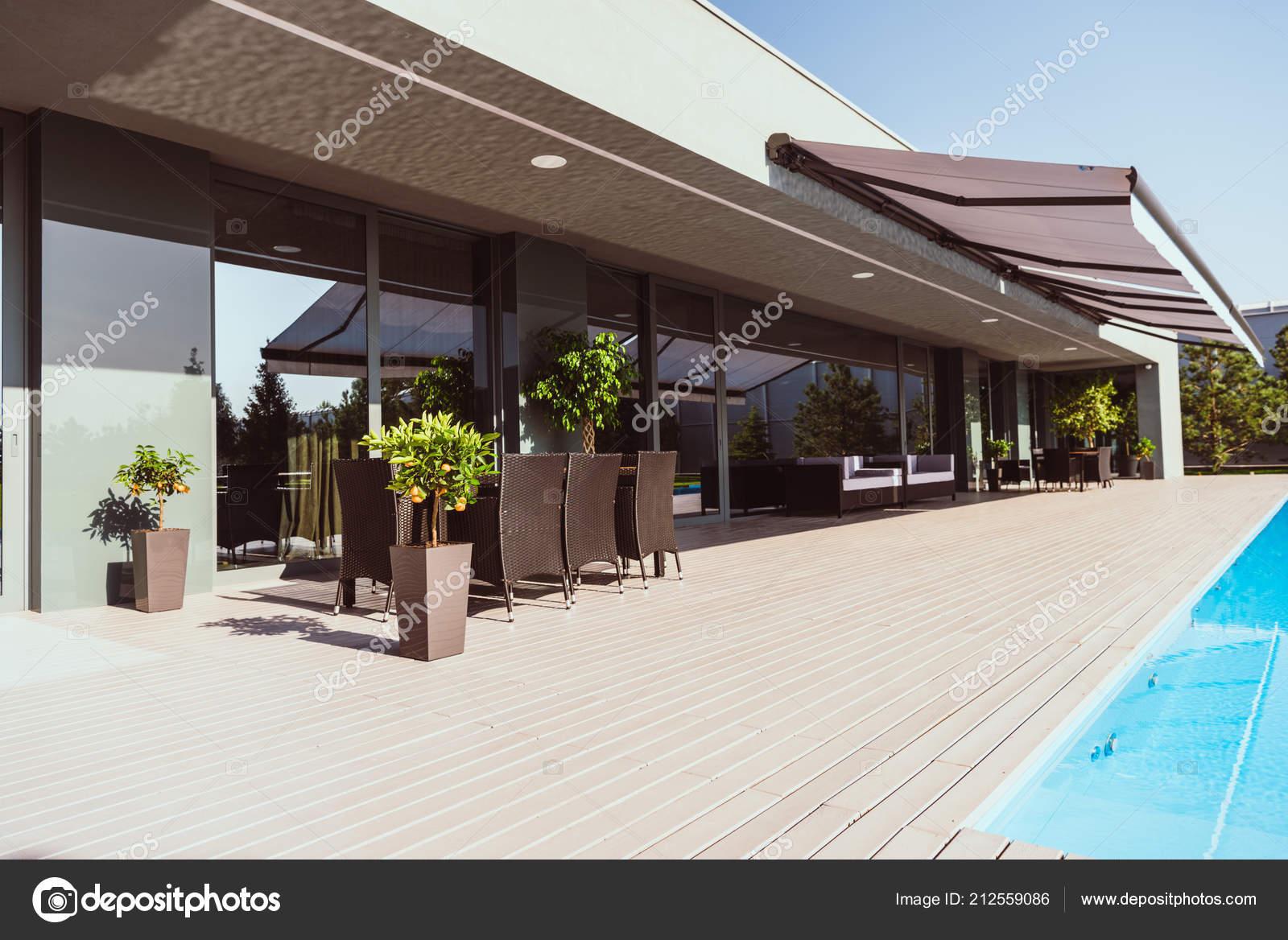 Zwembad overdekte terras van modern plattelandshuis met weinig