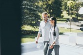 Photo smiling couple in sunglasses walking at country house