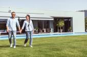 Fényképek mosolyogva pár gazdaság kezét, és séta a zöld gyep közelében uszoda: country house
