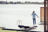 zadní pohled na dospělého muže na smartphone jezera v country house