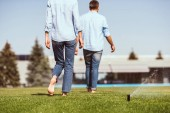 Photo partial view of couple waking on green lawn near country house
