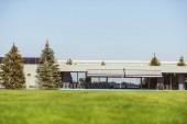 Fotografie Oberflächenniveau des grünen Rasens und modernes Ferienhaus unter blauem Himmel
