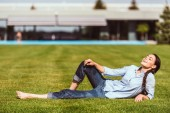Photo selective focus of happy young woman resting on grass in front of country house