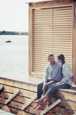 happy couple looking at each other and sitting on wooden pier near lake