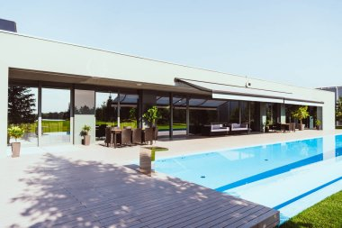 beautiful modern cottage with outdoors swimming pool under clear blue sky