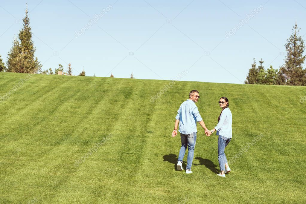 stylish couple in sunglasses holding hands and looking at camera on grassy hill outdoors