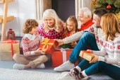 Photo beautiful happy family with gift boxes sitting on floor of living room during christmas