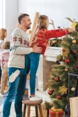 Photo parents and kids decorating living room together on christmas