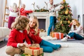 Fotografie happy siblings sititng on floor together with gifts during christmas eve