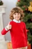 entzückende glückliches Kind Daumen mit unscharfen Weihnachtsbaum im Hintergrund auftauchen