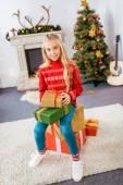 imádnivaló boldog gyermek ül a halmozott karácsonyi ajándék dobozok