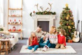 Fotografie parents and kids sitting on floor together on christmas at home