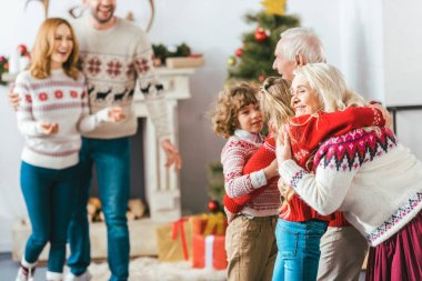 grandparents embracing with kids during christmas eve at home