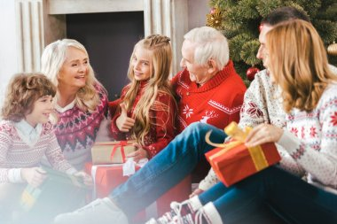 happy family with gift boxes sitting on floor of living room during christmas