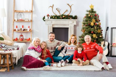 happy family sitting on floor together at home on christmas