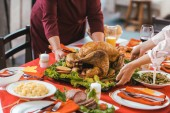 cropped shot of women serving tray wih turkey on thanksgiving table