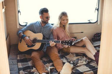 happy boyfriend playing on guitar while girlfriend holding vinyl record inside campervan