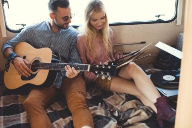 happy musician playing on acoustic guitar while girl holding vinyl record inside campervan