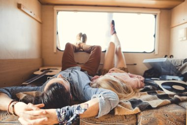 hippie couple lying inside campervan with acoustic guitar and vinyl player
