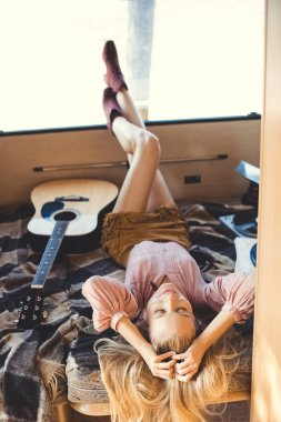 hippie girl relaxing inside trailer with acoustic guitar and vinyl player