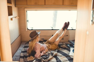 hippie girl in hat resting inside camper van with vinyl player and records