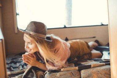 beautiful hippie girl in hat lying inside camper van