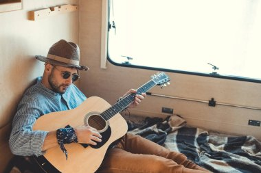 handsome man in hat playing guitar inside of campervan