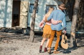 Photo rear view of hippie couple hugging and walking with guitar near trailer