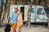 Photo hippie couple in sunglasses hugging and walking with acoustic guitar near trailer in forest