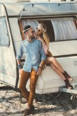 Photo hippie couple in wreaths and sunglasses looking at each other and sitting on trailer