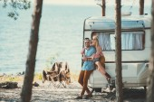 Photo happy hippie couple in wreaths hugging and sitting on campervan near sea
