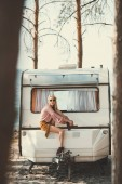 Photo young hippie woman in wreath and sunglasses sitting on trailer