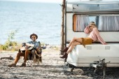 Fotografie hippie girl sitting on campervan while man playing acoustic guitar near