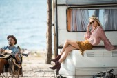 Photo hippie girl sitting on campervan while her boyfriend playing guitar near the sea