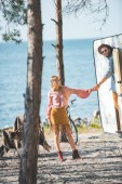 Photo hippie couple holding hands and going for a walk at campervan near sea