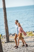 Photo beautiful hippie couple holding hands and walking in nature near sea