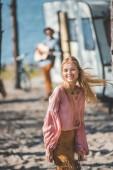Photo smiling hippie girl dancing while man playing guitar near campervan