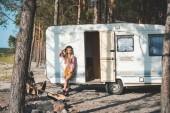 Fotografia ragazza bellissima hippie che posa vicino al furgone di campeggiatore in foresta