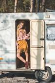 Photo attractive hippie girl in hat posing in door of camper van